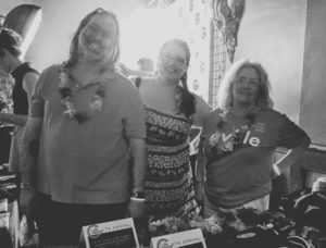 Elena and other volunteers selling merchandise at a fundraiser concert