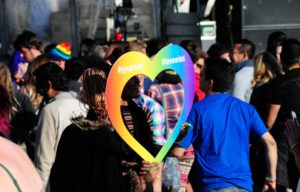 African American man with rainbow heart in croud
